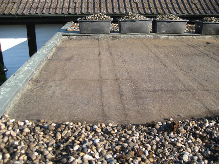 Ein undichtes Dach einer Doppelgarage soll abgedichtet werden. Der Kies wurde bereits abgeräumt