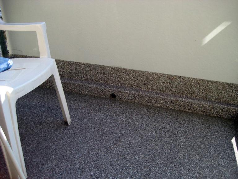 Sanierter Balkonboden mit eingedichtetem Bodenablauf. Der erhöhte Sockel schützt von Spritzwasser